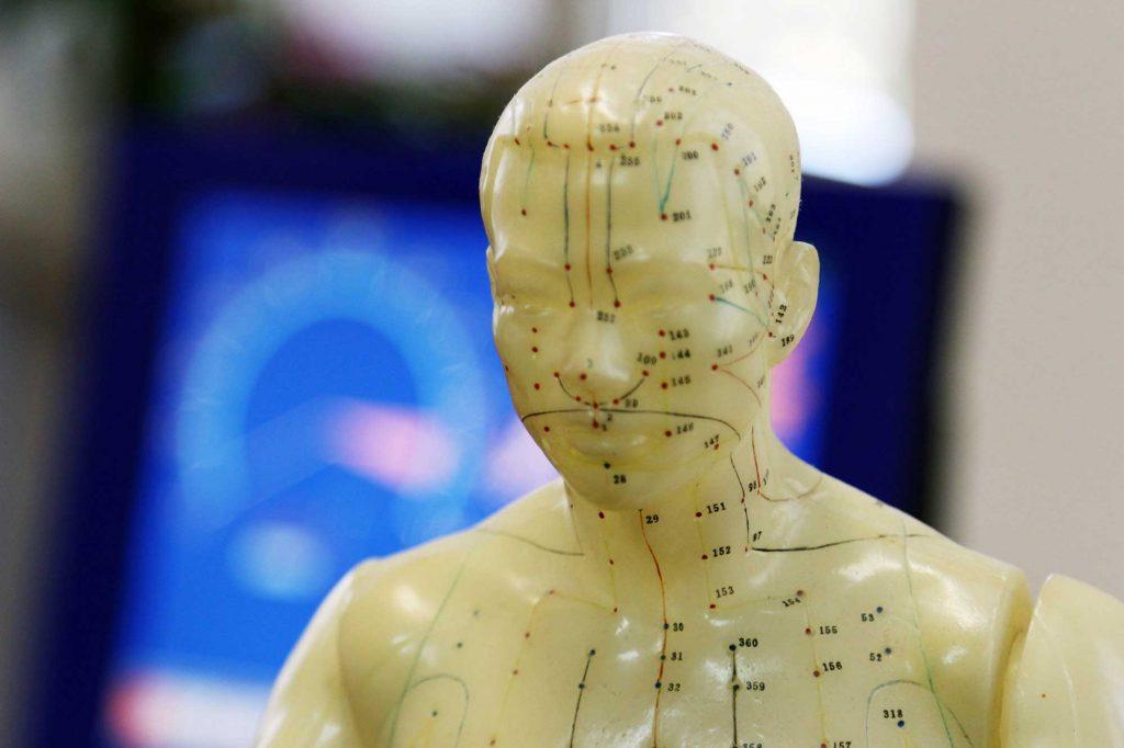 Kleine Wachsfigur mit Akupunkturpunkten vor einem Elektroakupunktur nach Voll Diagnosegerät